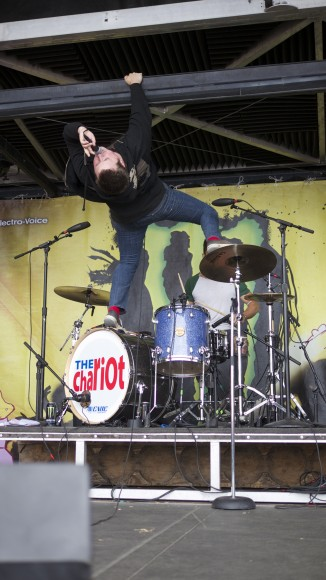 Drummer David Kennedy continues their set as lead vocalist Josh Scogin climbs atop Kennedy's drum kit.